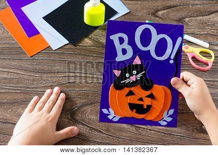 The Child Create A Birthday Card For Halloween Paper Black Cat In Pumpkin. Glue, Scissors, Leaves Ve
