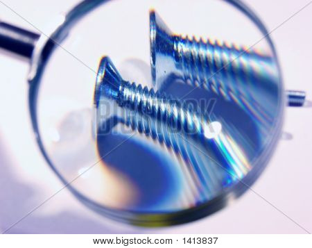 Two Screws Under A Magnifier.Checking The Quality.