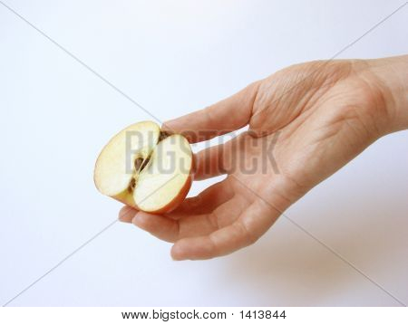 A Female Hand Holding A Part Of An Apple