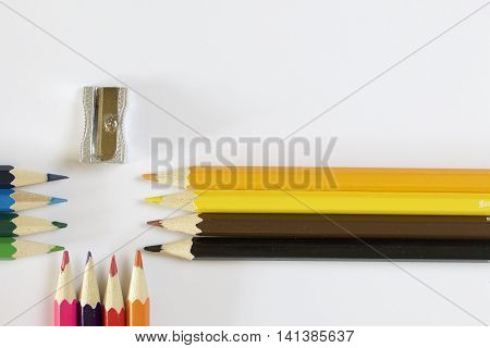 Colored pencils and sharpener. Located sharpened part of each other. On a white background.