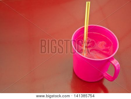 Cool water in pink plastic cup on red table