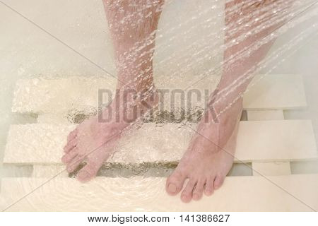 man washes his feet in the shower body care