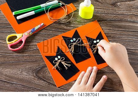 The Child Create A Greeting Card Halloween Black Cat Out Of Paper, Glues The Paper Parts. Glue, Scis