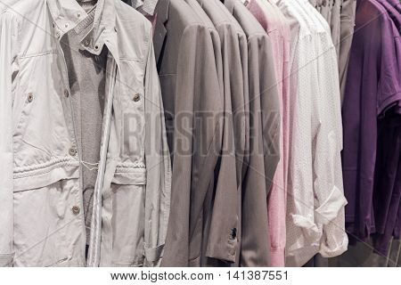 Rail With Assortment Of Men Jackets Of Pastel Color Hanging Inside Clothing Store With Electric Lighting Close Up