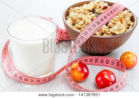 Beautiful plate with muesli, glass of milk, plums and meter tape