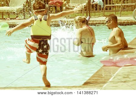 Young Parents enjoying time at the swimming pool with their children. Retro instagram look.