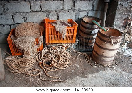 Fisherman's storage. Old two wooden barells net stored in fish crates ropes.