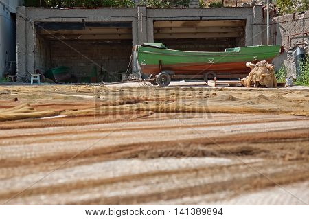 Fishing boats and nets. The nets are dried and stored. Fishing nets on the storage after fishing day.