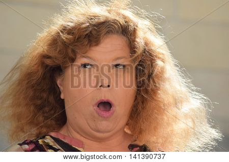 Middle aged woman who is shocked with a surprised facial expression