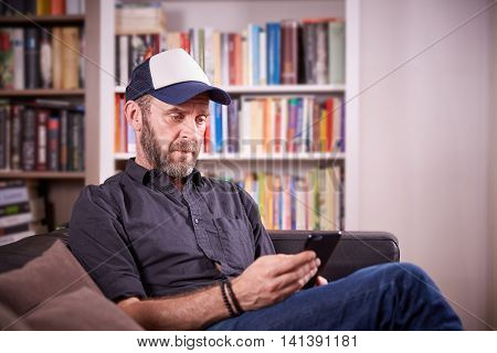 Isolated man sitting on a couch in front of bookshelf pondering