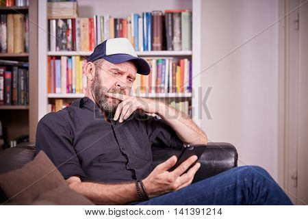 Man Sitting On Couch In Living Room Looking On Mobile Phone Brooding And Looking Seriously