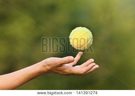 hand tossing tennis ball on green blurred background