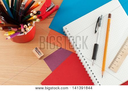 Colored pencils notebook ruler and pen on the table