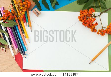 Colored pencils and paper on the table. Photos school supplies