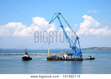 Floating crane and marine tug in the port of Russia