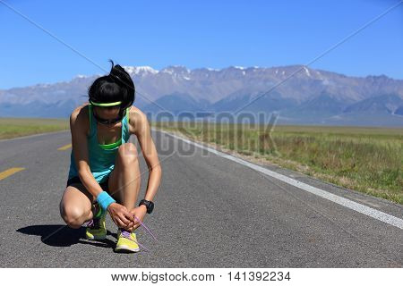 young fitness woman runner tying shoelace on road