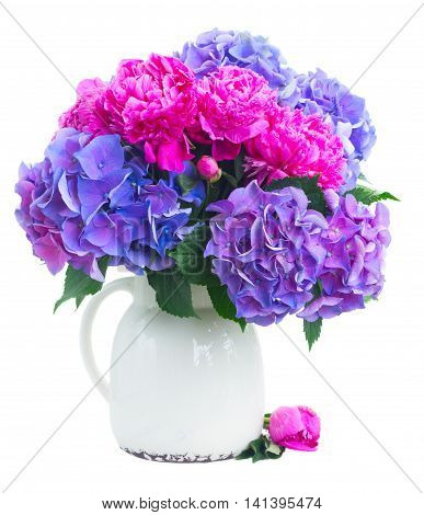 Bright pink peony, eustoma and blue hortensia fresh flowers bouquet in vase isolated on white background