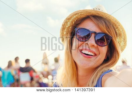 Young beautiful woman taking a selfie at the beach bar