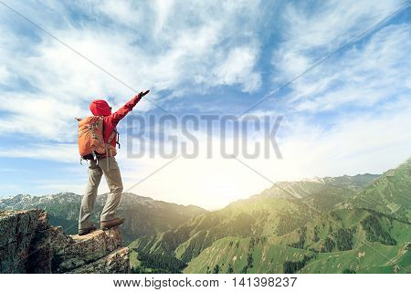 cheering young woman backpacker open arms on mountain peak cliff