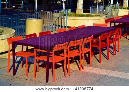 Outdoor furniture including colorful chairs and a table taken in a courtyard at a park