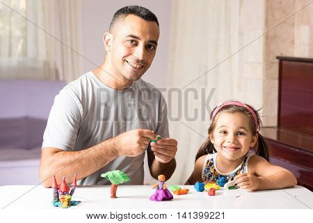 Little Girl Is Playing With Putty Together With Her Father