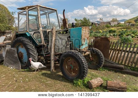 tractor stands near a fence in the village