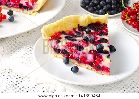 Mix berry tart, pie, cake with raspberries, bilberries, bluberries, red currant and cream on white background, toned