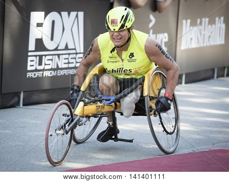 NEW YORK JUL 24 2016: ParaTriathlete from Achilles International nears the finish line in Central Park in the NYC Triathlon Race, the only International Distance triathlon in the city.
