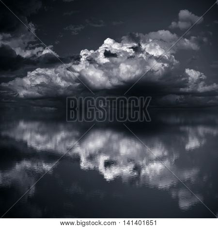 Dark clouds over sea. Imitation black and white photo
