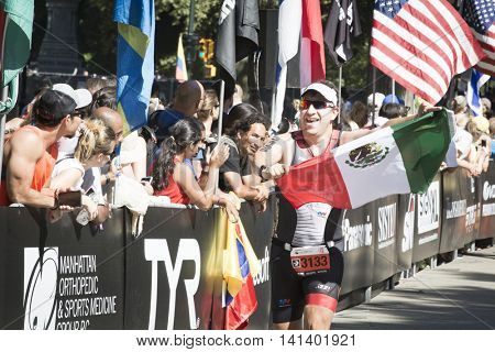 NEW YORK JUL 24 2016: Athlete approaching the finish line of the NYC Triathlon Race in Central Park. The run is 10 kilometers and the race is the only International Distance triathlon in the city.