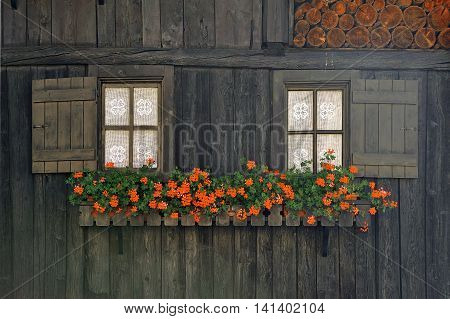rural wooden facade with windows and flowers in alps town Rhemes Notre Dame in Valle d'Aosta Italy