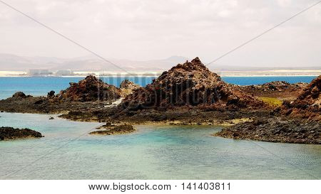 View on the lagoon with emerald water and dark volcanic rocks on the Canary island Lobos with the island Fuerteventura on the background.