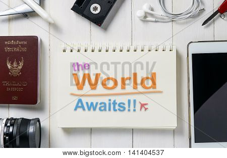 The World awaits text on a book for travel agency banner website.