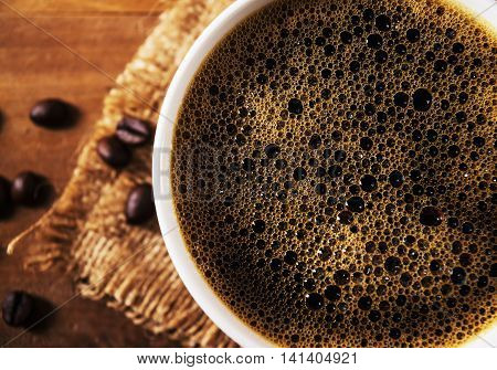 Closeup coffee cup with coffee bean on brown wooden table in still life and filter color tone
