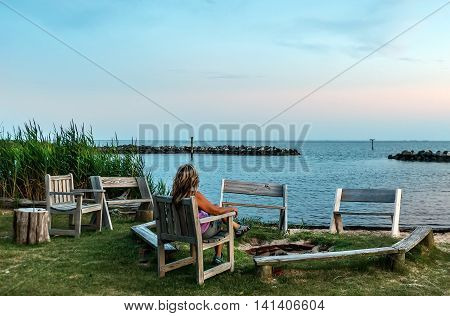 Female relaxing in a chair on a Chesapeake Bay beach watching a sunset