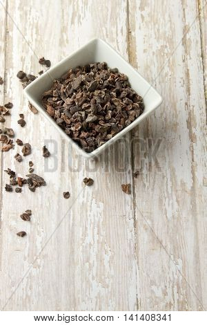 Bowl Of Organic Cacao Nibs On A Wood Plank Board