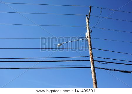 power pole under blue sky, vertical composition