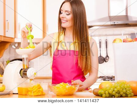 Woman Making Orange Juice In Juicer Machine