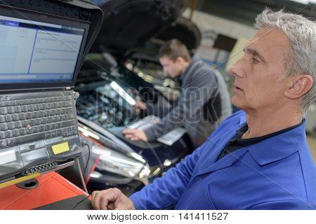 professional car mechanic at his workplace preparing checklist