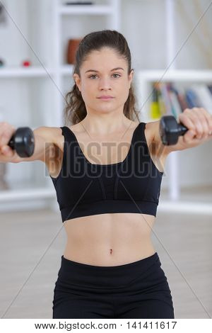 beautiful athletic woman pumping up muscules with dumbbells in gym