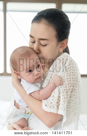 Picture of happy Asian mother kiss infant baby boy after cry. Closeup at mother and infant baby.