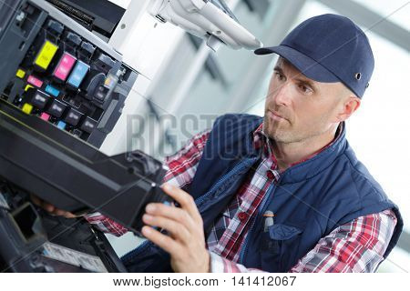 man technician repairing a printer at business place at work