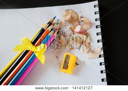 bunch of colored pencils sharpened with a yellow bow, sharpener and shavings on a white notebook