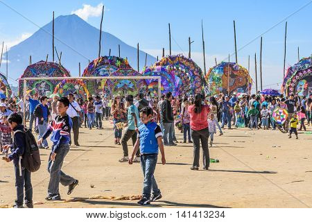 Sumpango Guatemala - November 1 2015: Visitors at giant kite festival honoring spirits of the dead on All Saints' Day. Agua volcano in background.