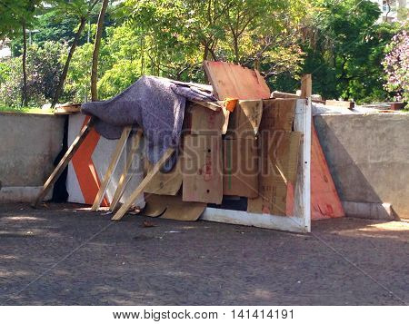 Homeless person's house in Brazil made of cardboard boxes and a blanket in the centre of a city at the edge of the sidewalk.