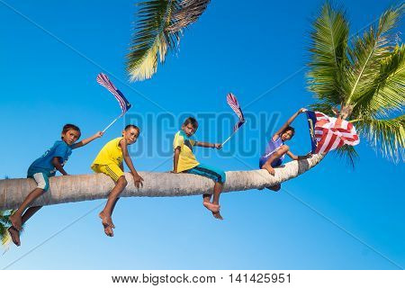 Semporna, Sabah, Malaysia - 06 Ogos 2016: Dramatic view group patriotic kid boy climb a coconut tree with they national flag of Malaysia with amazing view background, clean beach , blue sky background