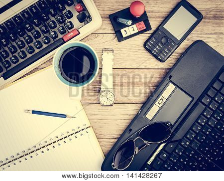 Office desk background. Coffee notepad pencil wristwatch laptop sunglasses mobile phone and typewriter on vintage wooden desk