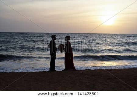 COLOMBO SRI LANKA - AUG 18 2005: married couple stands happy and romanticly at the beach on their wedding day in sunset