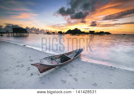 Beautiful hue of sunrise at Maiga Island with silhouette of seagypsy village and old wooden boat located at Semporna, Sabah, Malaysia. Rarely seen sunrise at the island, especially the colour.