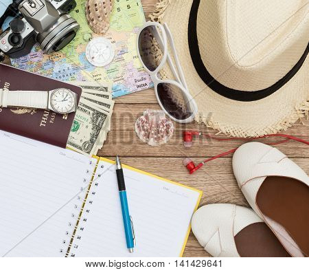 Travel concept with digital camera straw hat sunglasses world map compass passport money wristwatch shoes earphones notepad pen and seashell on wooden table
